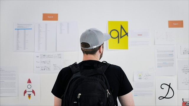 ein Mensch mit Rucksack vor einer Pinnwand mit Zetteln/A person with a backpack in front of a bulletin board with lots of notes