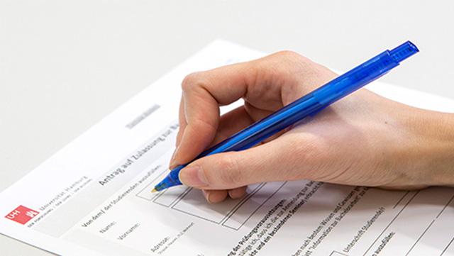 Rechte Hand mit blauem Kugelschreiber beim Ausfüllen eines Formulars