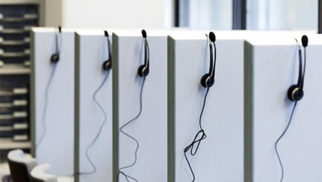 Hellgraue Trennwände im Telefonlabor, auf denen Kopfhörer für Umfragen sind