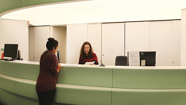 Mitarbeiterin im Studienbüro mit Zettel in der Hand sitzt hinter dem grünen Tresen und Studierende mit hochgesteckter Frisur steht vor dem Tresen