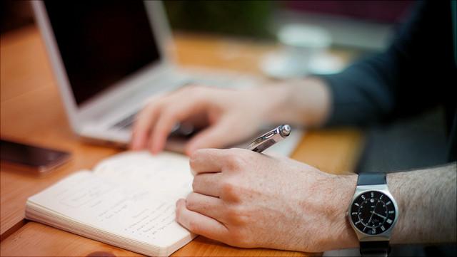 Jemand schreibt etwas in ein Notizheft, ein Laptop liegt daneben