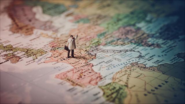 Die Miniatur-Figur eines Mannes mit Mantel und Koffer steht auf einer Landkarte