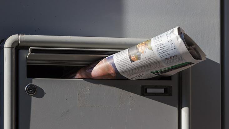 Zeitung guckt halb aus dem Briefkasten heraus.