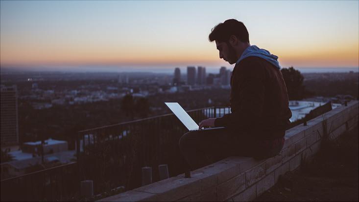 Mann arbeitet auf dem Dach mit Laptop