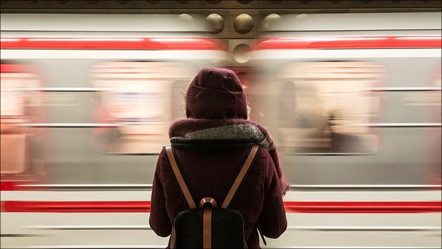 Eine Person steht am Gleis, der Zug fährt an ihr vorbei