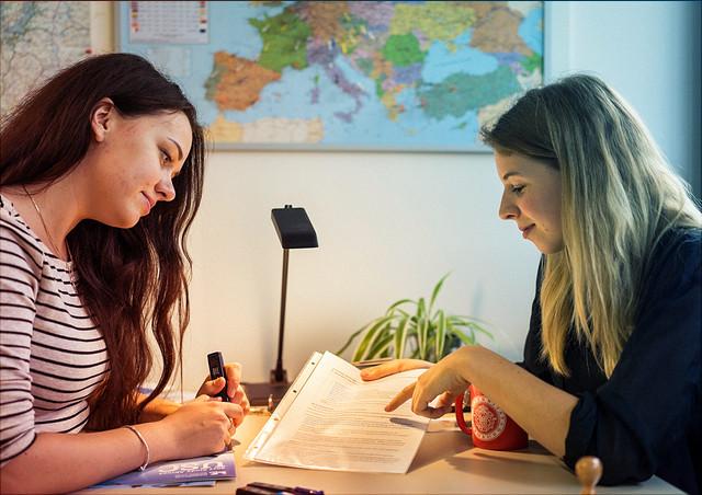 Eine junge Frau zeigt einer anderen ein Dokument in einem Büro mit einer Landkarte an der Wand