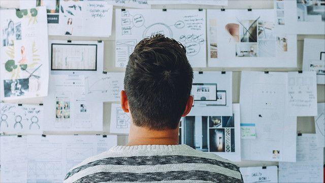 Mensch blickt auf eine Pinnwand mit Zetteln/Person looking at a bulletin board with notes