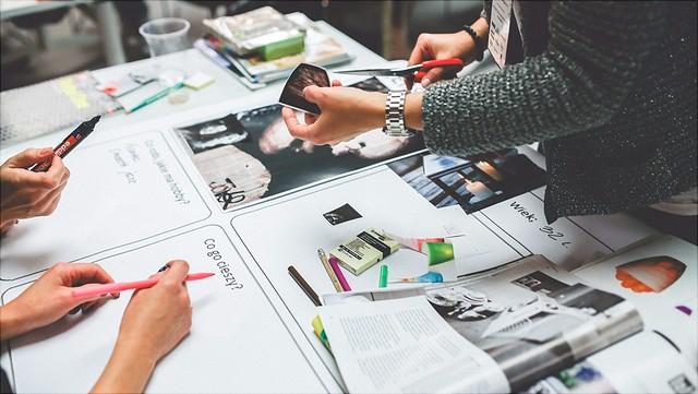 Drei Personen arbeiten an einem Tisch bedeckt mit Zeitungsschnipseln, Stiften und Scheren/three people work at a desk covered with newspaper clippings, markers and scissors