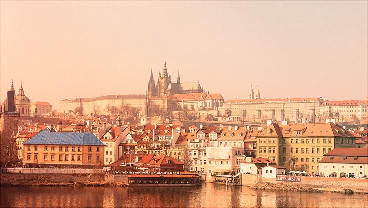 Ansicht auf Prag über die Moldau, man sieht bunte alte Häuser und Kirchen