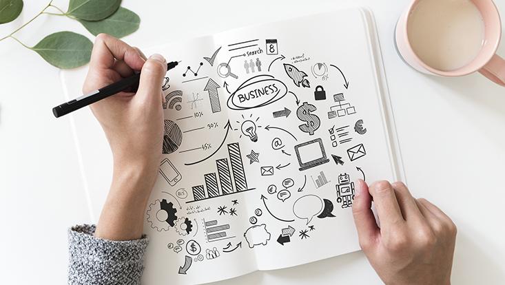 Eine Frau hält mit der linken Hand einen Stift und skizziert in einem Notizblock ihre Pläne für ein Start-Up. Rechts neben dem Block steht ein Becher Milch.