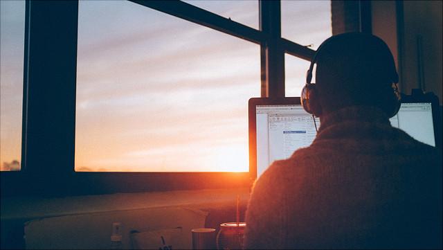 Ein Mann, der Kopfhörer trägt, sitzt an einem Schreibtisch. Durch eine Fensterscheibe sieht man die untergehende Sonne.