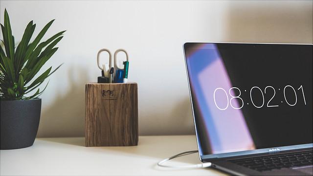 Rechts auf einem Schreibttisch steht ein Laptop, der eine Uhrzeit anzeigt. Daneben stehen eine Box mit Schreibtischutensilien und eine Topfpflanze.