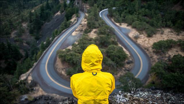 Ein Mensch in einer gelben Regenjacke sitzt vor einer Straße, die eine scharfe Kurve macht.