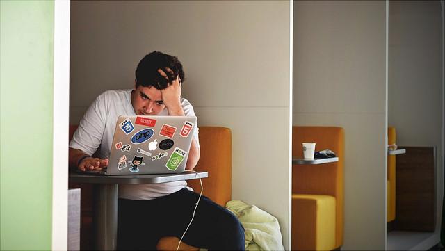 Ein junger Mann sitzt an seinem Laptop in einem Café und streicht sich dabei nervös durch die Haare.