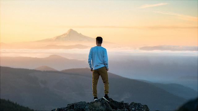 Ein Mann steht vor einer nebligen Gebirgslandschaft.