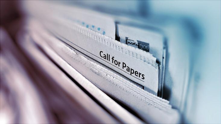 """Ein Stapel Zeitungen. Auf einer davon steht """"Call for Papers""""."""
