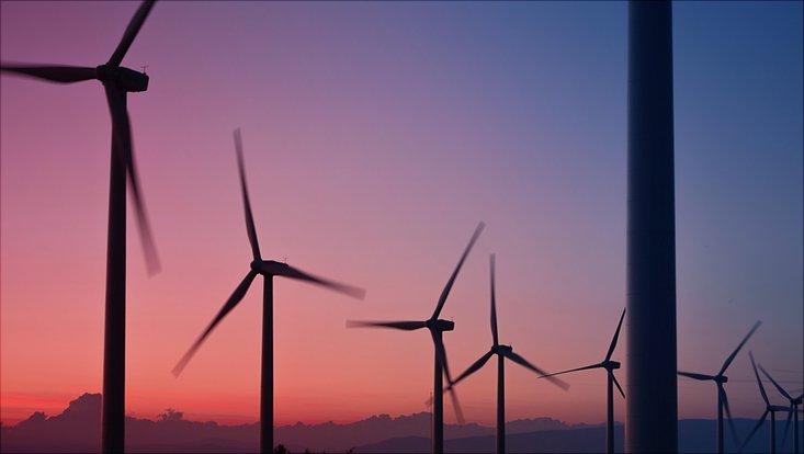 Windräder auf einer Anhöhe bei Sonnenuntergang