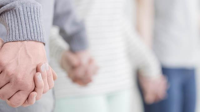 Auf diesem Bild sind mehrere Menschen zu sehen, die in einem Kreis stehen und sich die Hände halten.