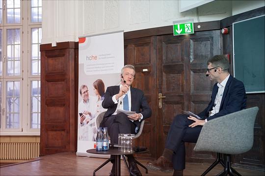 Zwei Redner interviewen sich gegenseitig im Sitzen auf einer Bühne.