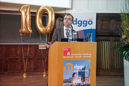 Ein Redner steht am Pult vor einem Ballon, der die Form einer 10 hat.