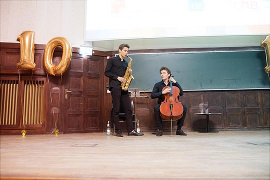 Ein Saxophonist und ein Cellist spielen neben einem Ballon, der die Form einer 10 hat.