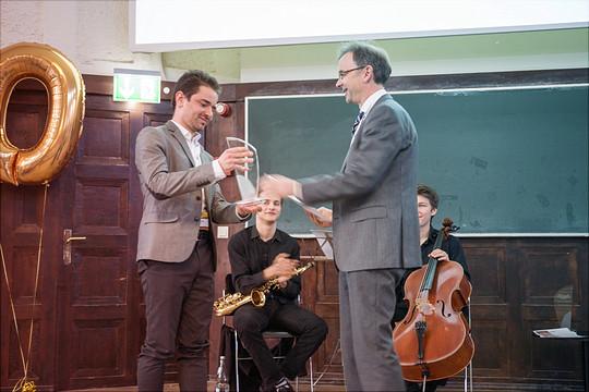 Ein Dozent überreicht einem Teilnehmer ein Preis.
