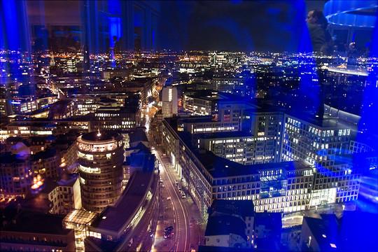 Foto aus einem Fenster in die beleuchtete Nacht Hamburgs. Im Fenster spiegelt sich das blaue Licht des Raums.