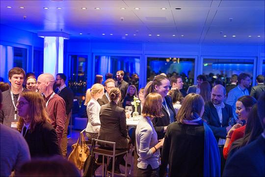 Eine große Gruppe von Gästen auf einer Party an einem blau beleuchteten Veranstaltungsort.