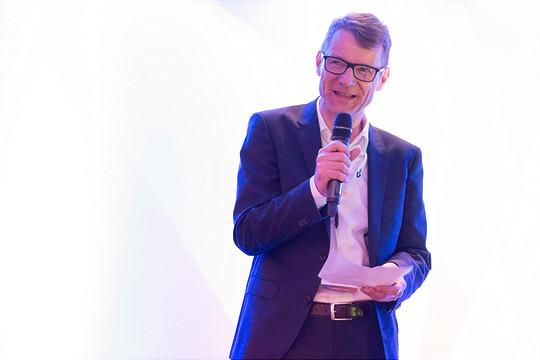 Ein Mann in Anzug moderiert ein Event.