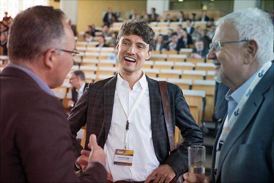 3 Männer unterhalten sich im Rahmen einer Veranstaltung in einem Hörsaal.