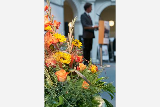 Ein Blumengesteck auf der Bühne im Altbau der Staats- und Universitätsbibliothek, im Hintergrund der Direktor der Graduate School Prof. Dr. Timo Busch