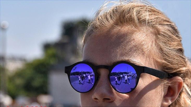 Menschen spiegeln sich in einer Sonnenbrille