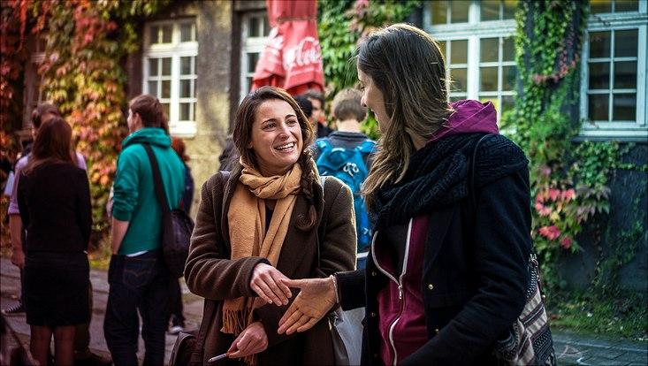 Zwei Frauen reichen sich vor dem Unihauptgebäude die Hände zur Begrüßung.