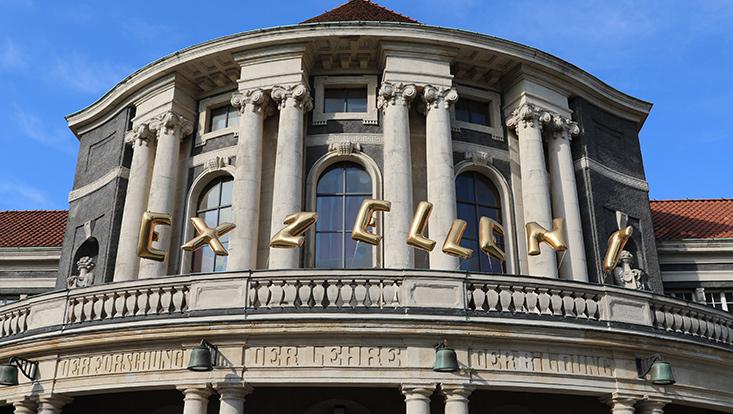 Goldene Buchstabenballons bilden das Wort Exzellent am Hauptgebäude der Universität Hamburg