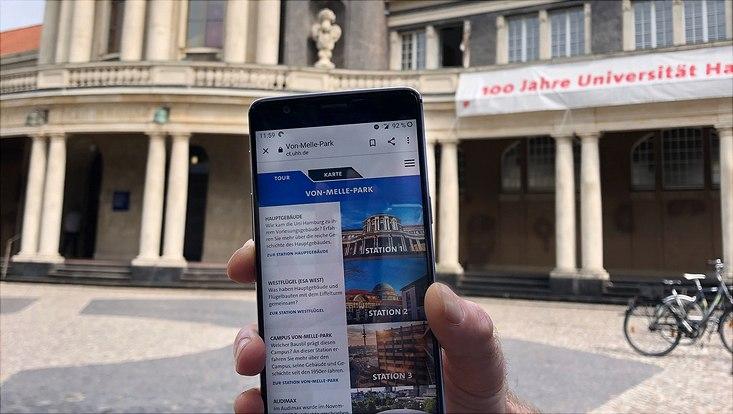 Smartphone mit der Campus-Tour vor dem Hauptgebäude der Universität Hamburg.