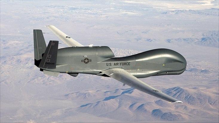 Eine amerikanische Drohne kreist über einem kargen Gebirge.