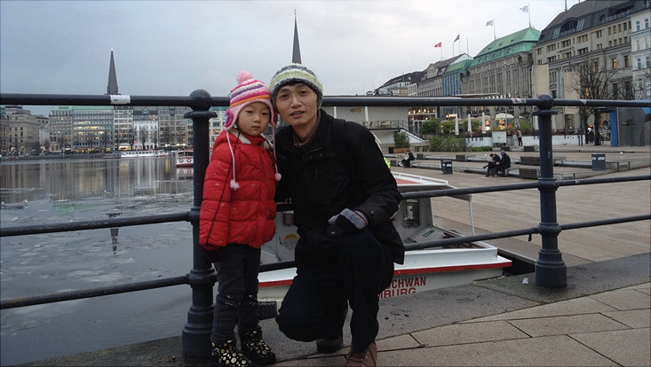 Mr Fei with his child in front of water and buildings in winter