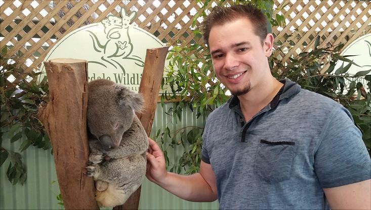 male student posing with a koala