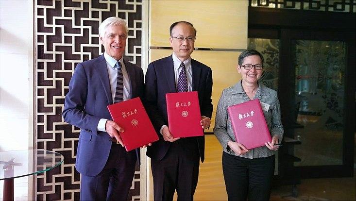 Three university representatives presenting joint contract