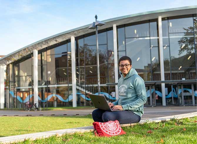 Student mit Laptop vor dem Audimax der Universität Hamburg