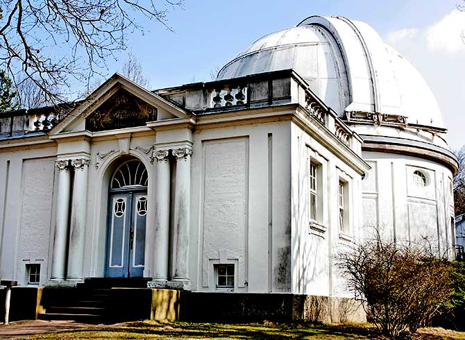 Weißes Gebäude der Hamburger Sternwarte mit Refraktor
