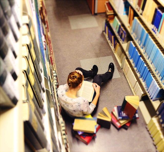 Studentin liest Buch in Bibliothek