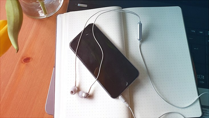 Ein Mobiltelefon mit angeschlossenen Kopfhörern liegt auf einem Notizbuch.
