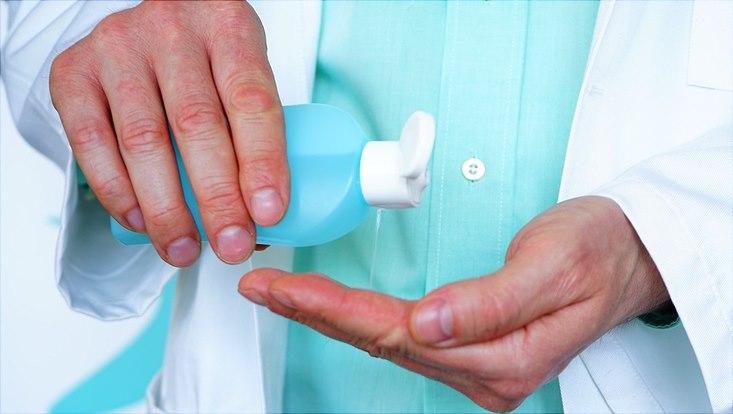 Hände, die Desinfektionsmittel aus einem Fläschchen verwenden