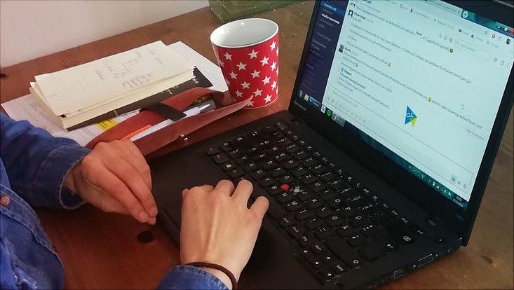 Schreibtisch mit Laptop, auf dem gerade zwei Hände tippen