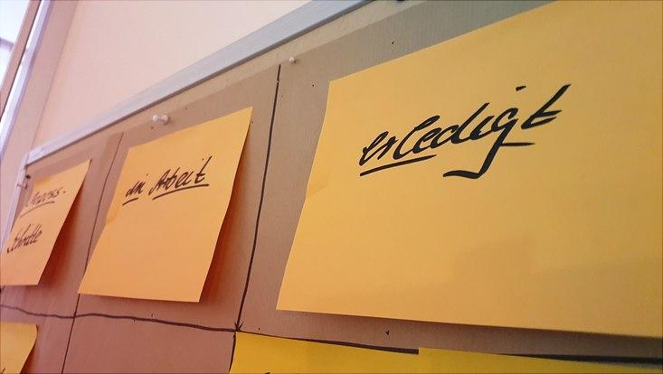 """Gelbe Post-its auf einer Pinnwand, beschrieben mit """"in Arbeit"""" und """"erledigt"""""""