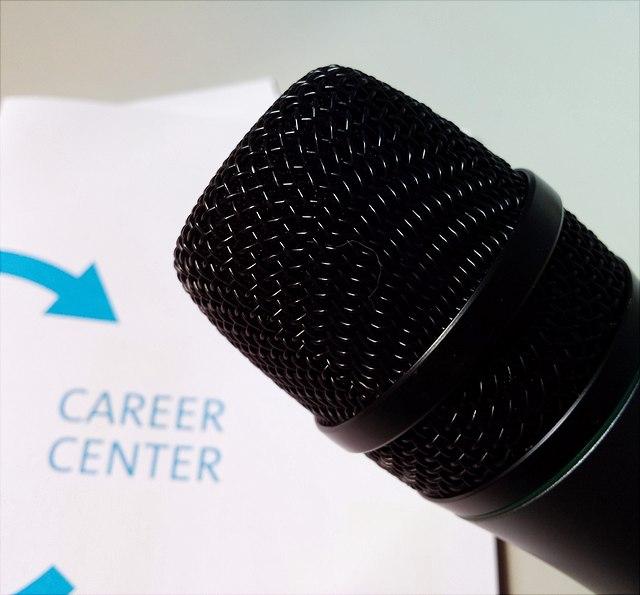 """Mikrofon vor einem Titelblatt des Career Center-Programmhefts mit der Aufschrift """"Career Center"""""""