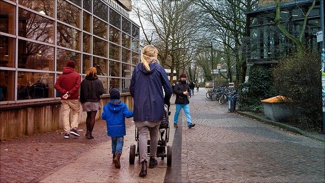 Eine Kind mit Kinderkarre und Kleinkind geht über den Campus