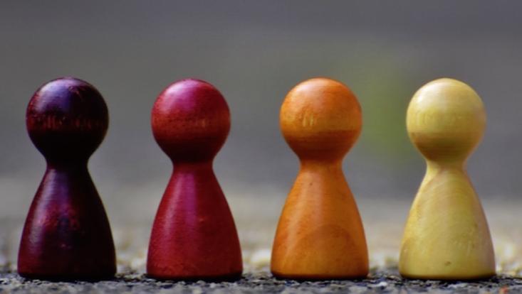 4 Spielfiguren auf einer Linie nebeneinander. Die Figuren haben unterschiedliche,rötliche Farben und stehen auf einem dunklen Untergrund