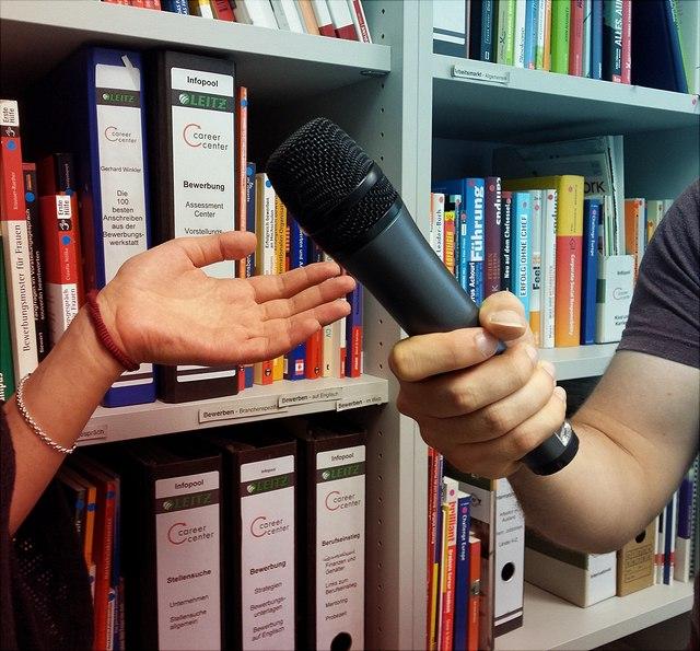Zwei Hände, eine hält ein Mikrofon